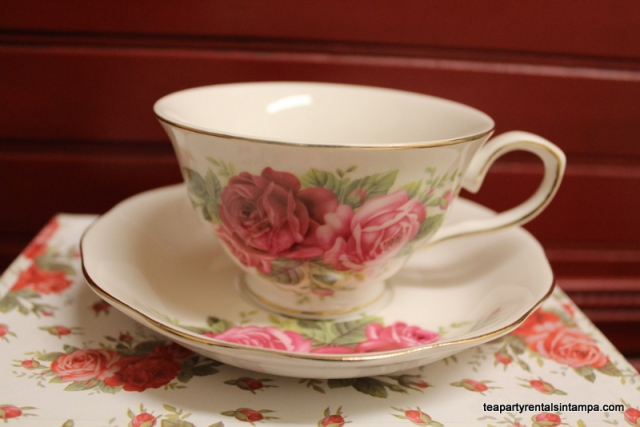 Teacup and saucer rose buds, red beadboard background