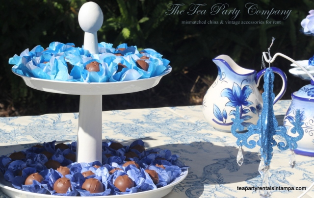 candy buffet display ,chocolate wrapped blue paper 2 tiered plate,glitter blue hanging candelabra,toile motif tablecloth